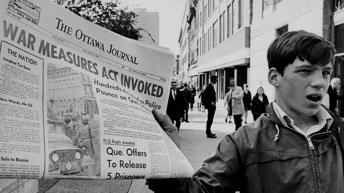 A newsboy holds up a newspaper with a banner headline reporting the invoking of the War Measures Act on Oct 16, 1970, following the kidnapping of British diplomat James Cross and Quebec Labour Minister Pierre Laporte by the FLQ. CP