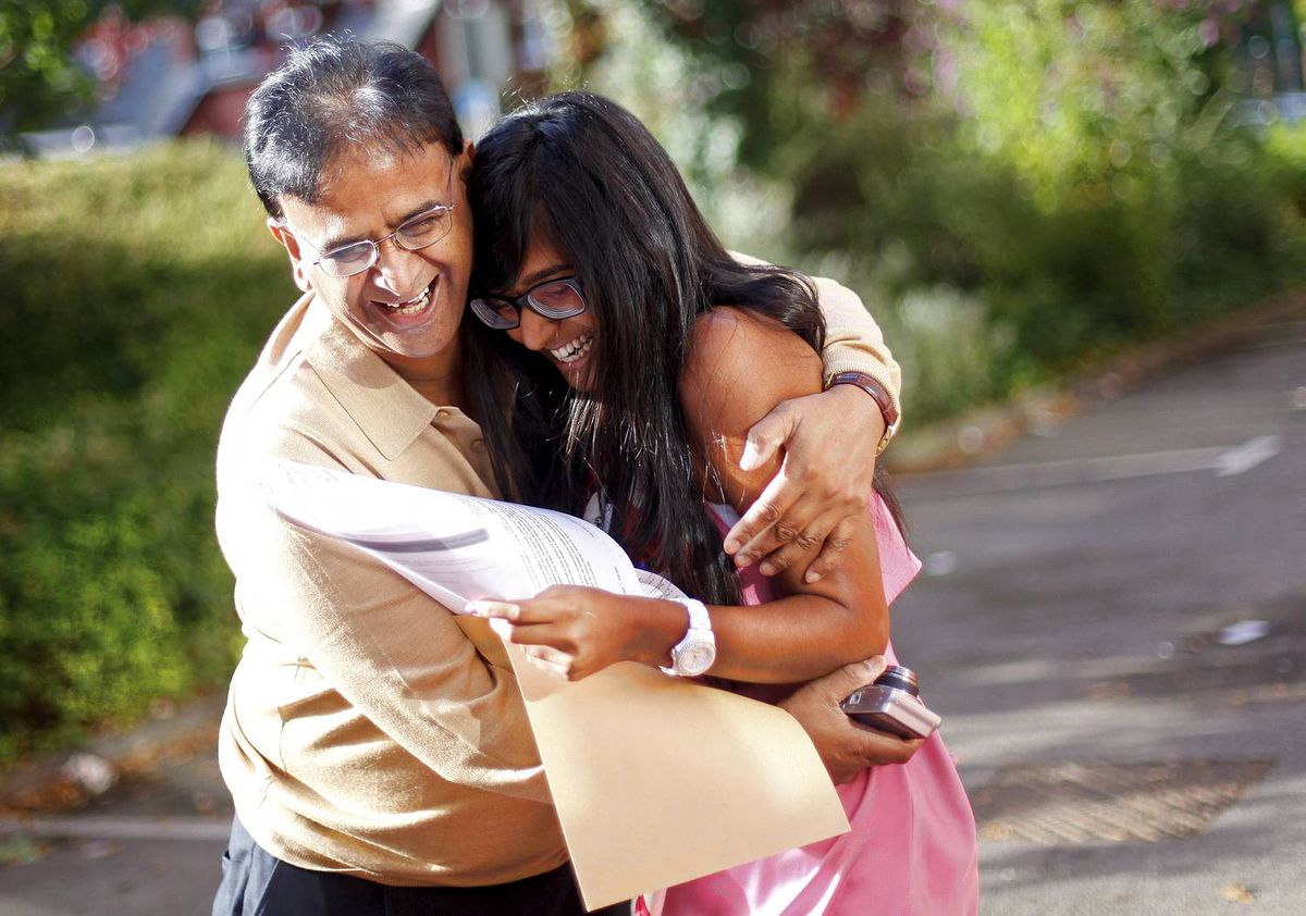 Anisha Patel celebrates with her father after opening her A-level exam results in Manchester