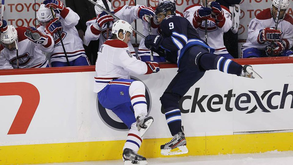 Winnipeg Jets forward Evander Kane takes out Montreal Canadiens defenseman Jaroslav Spacek in the first period of the inaugural game at the MTS Centre in Winnipeg, Sunday.