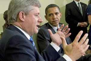 U.S. President Barack Obama looks on as Prime Minister Stephen Harper speaks to reporters in the Oval Office on Sept. 16, 2009.