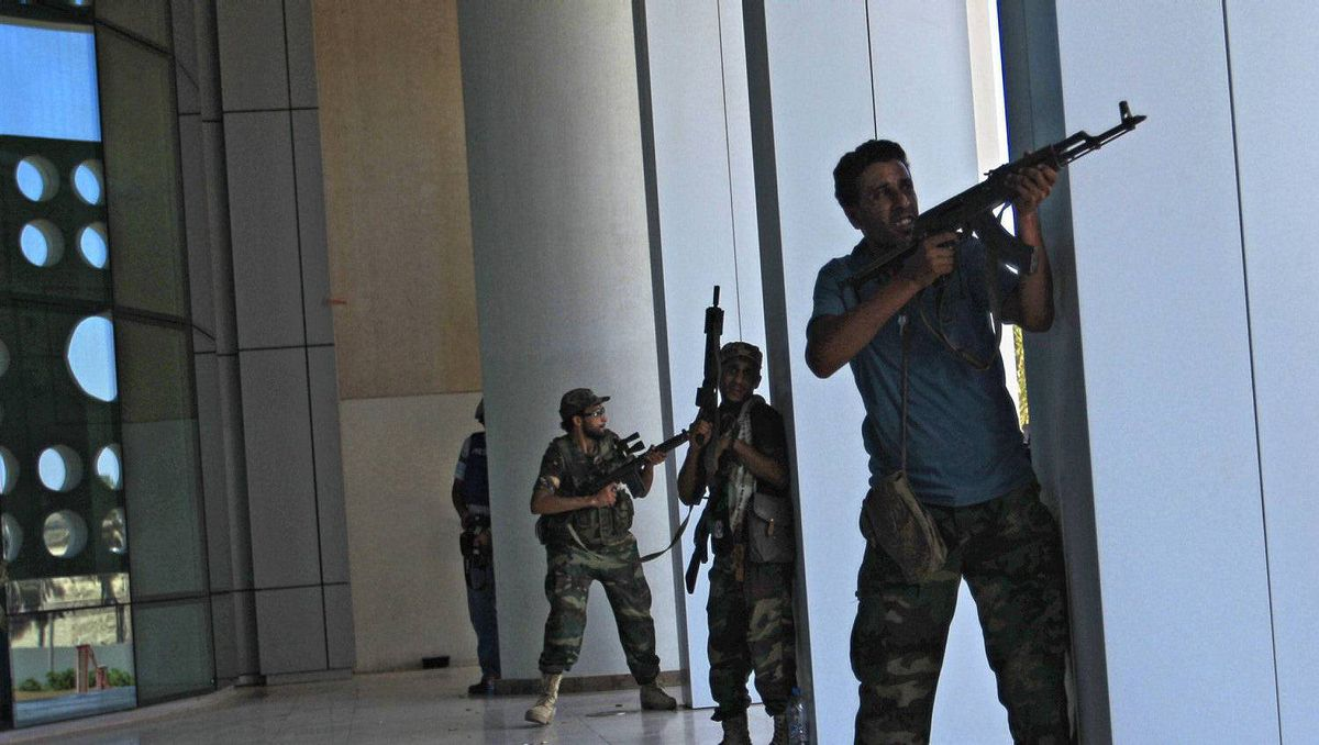 Rebel fighters take shelter as an intense gunbattle erupted outside the Corinthia hotel, where many foreign journalists are staying, in Tripoli, LIbya, Thursday, Aug. 25, 2011.