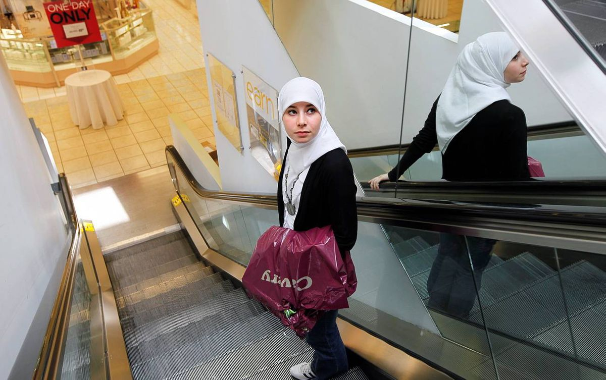Sarah Kassem holds her recently purchased prom dress as she rides the mall escalator.