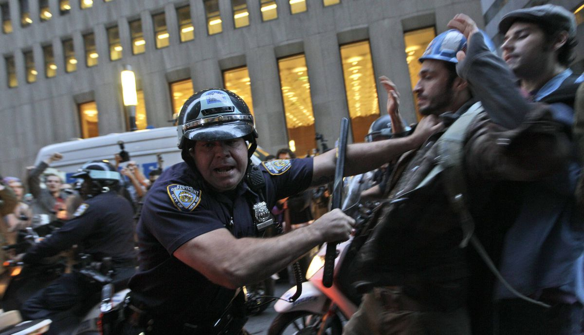 A New York City police officer shoves a demonstrator affiliated with the Occupy Wall Street protests as they march through the streets in the Wall St. area
