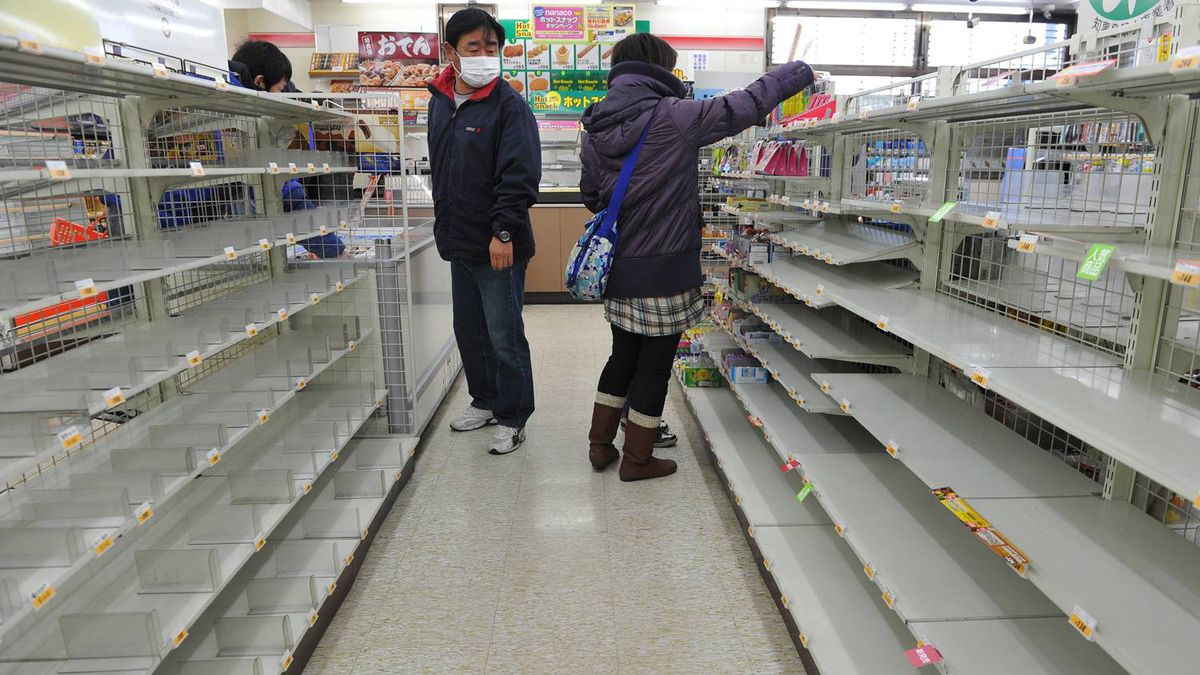 People look for food amid empty shelves in a shop in Fukushima on March 13, 2011. An explosion at the number one reactor fo the Fukushima nuclear plant triggered fears of a meltdown after a massive earthquake and tsunami left more than 1,000 dead and at least 10,000 unaccounted for. The panic has caused shortages of food and fuel in many parts of eastern Japan.