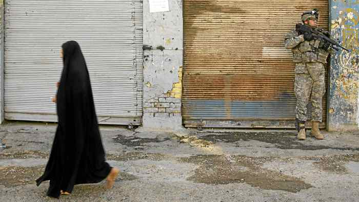 An Iraqi woman walks past a U.S. soldier on patrol in the Sheikh Ali Muslim Sunni neighbourhood in Baghdad in March, 2007.