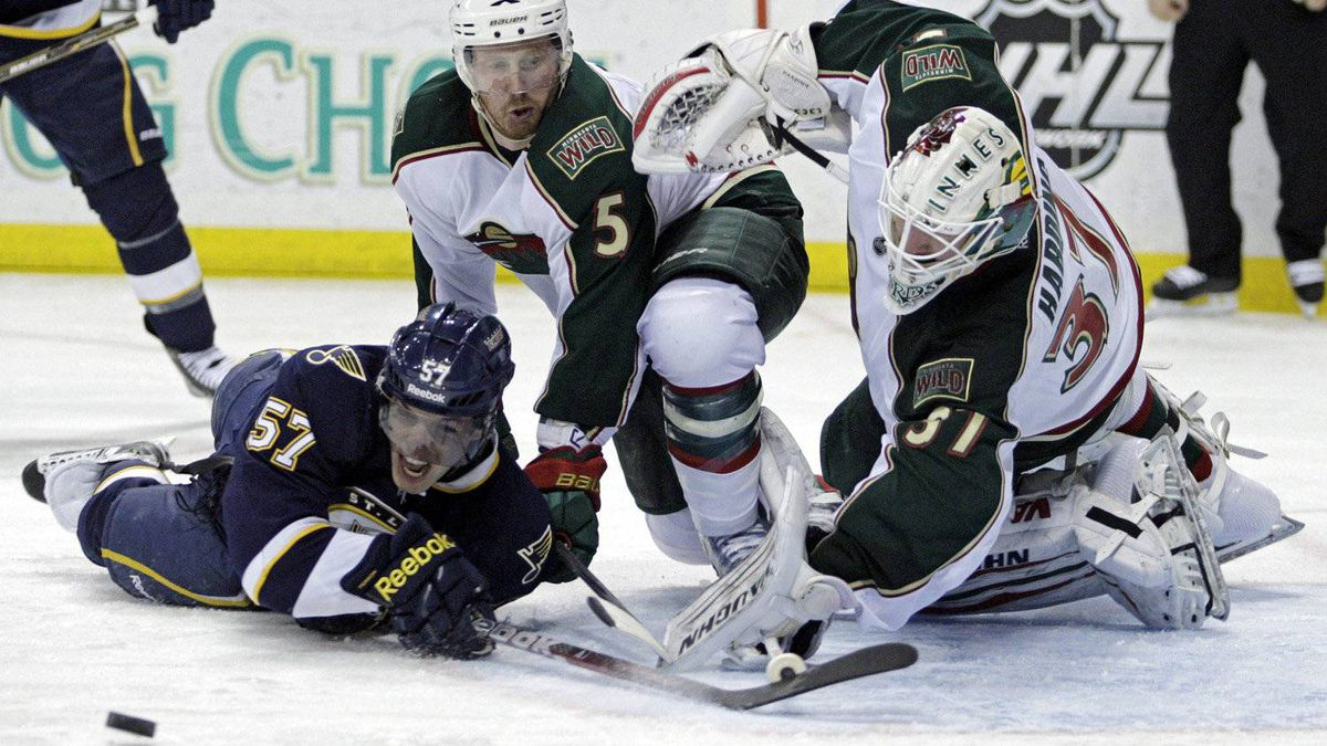 St. Louis Blues' David Perron (57) tries to direct the puck into the net while falling down as Minnesota Wild goalie Josh Harding (37) and Greg Zanon (5) defend in the second period of an NHL hockey game, Saturday, Feb. 18, 2012 in St. Louis. The Blues won 4-0. (AP Photo/Tom Gannam)