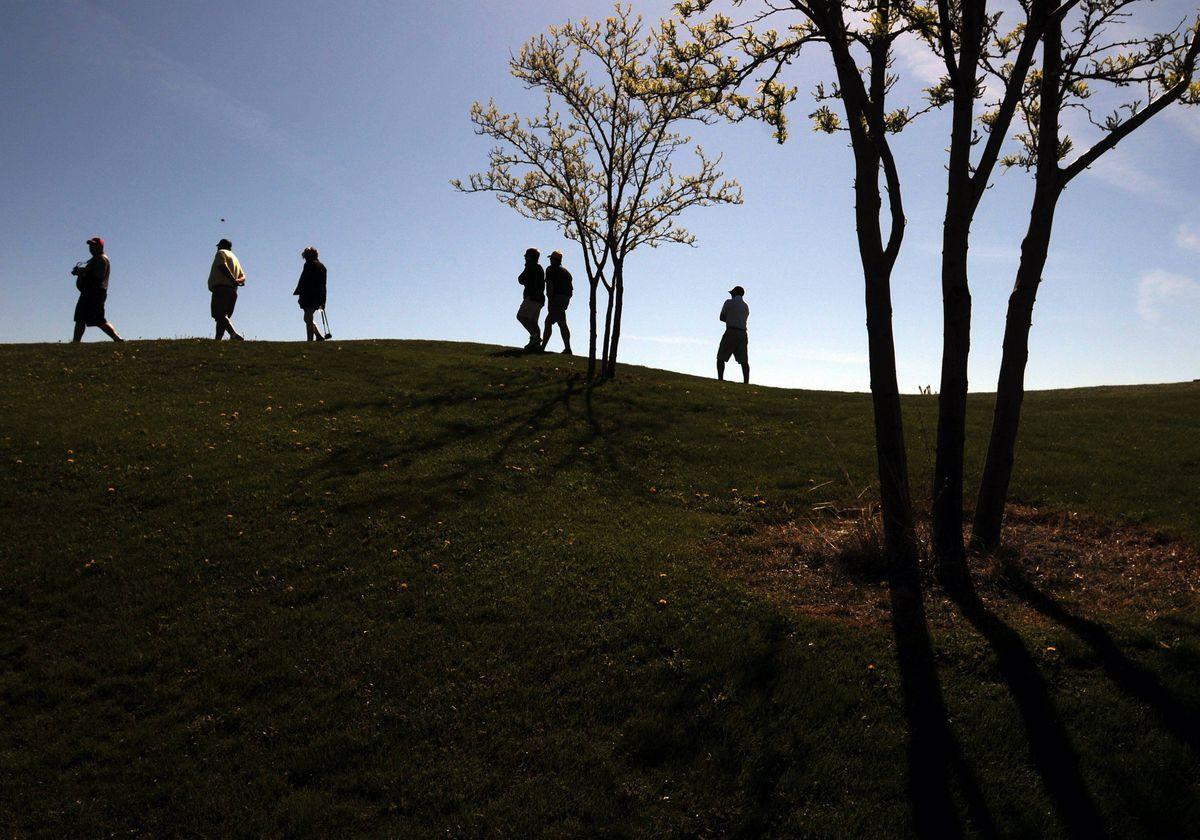 Spectators walk along a hillside as high school golfers tee off in the Idaho High School District III golf tournament at Falcon Crest Golf Club outside Kuna, Idaho.