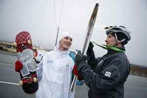 Gold-medal winning snowboarder Ross Rebagliati holds his skateboard and the Olympic torch as at the end of his leg of the relay in Osoyoos, B.C. on Jan. 25, 2010.