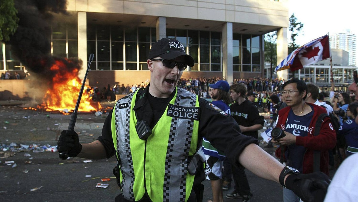 A Vancouver police officer waves a baton as he attempts to control the crowd during a riot after the Canucks lost Game 7 of the Stanley Cup Final to the Boston Bruins.