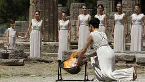 An actress playing the role of High Priestess, lights a torch from the sun's rays reflected in a parabolic mirror during the torch lighting ceremony of the London 2012 Olympic Games at the site of ancient Olympia in Greece May 10, 2012.