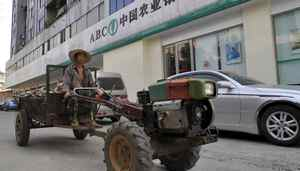 A farmer drives a tractor past a branch of Agricultural Bank of China in Xiangfan