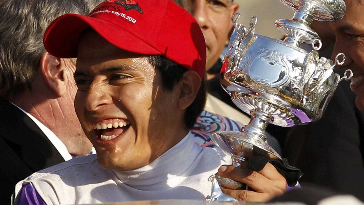 Jockey Mario Gutierrez holds the Woolawn Vase after winning the 137th Preakness aboard I'll Have Another at the 137th running of the Preakness Stakes at Pimlico Race Course in Baltimore, Maryland, May 19, 2012. REUTERS/Kevin Lamarque