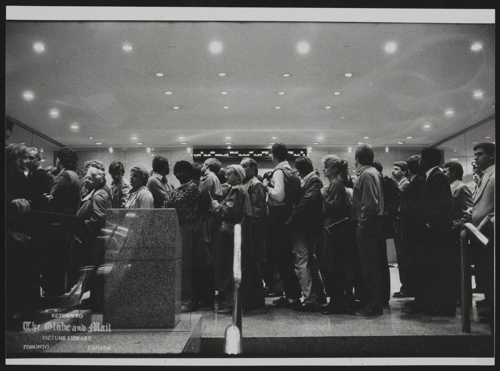 The notes transcribed from the back of this photograph are as follows: STOCK MARKET CRASH The continuing drama of the market drew crowds of the anxious and the curious to the Toronto Stock Exchange. Prices fell again yesterday.