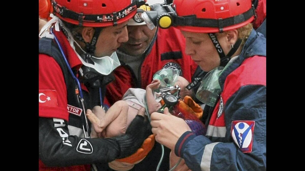 Turkish rescuers carry Azra Karaduman, a two-week-old baby girl they saved from the debris of a collapsed building in Ercis, Van, eastern Turkey. The baby's mother, Semiha, was still alive, pinned next to a sofa inside the flattened building from where the child was rescued.