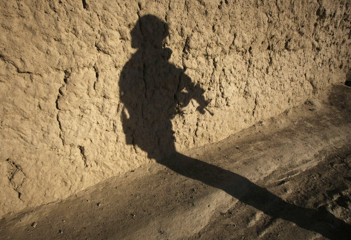 The shadow of a Canadian soldier from the NATO-led coalition is cast on a mud wall shortly before his patrol came under fire in the Taliban stronghold of Kolk in Zahri district, Kandahar province, southern Afghanistan, November 15, 2007.