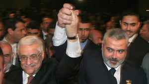 In this Saturday, March 17, 2007 file photo, Palestinian Authority President Mahmoud Abbas, left, and Prime Minister Ismail Haniyeh from Hamas, right, raise their linked arms as they move through the crowd at a special session of parliament in Gaza City. Palestinian officials from the rival Fatah and Hamas movements said Wednesday, April 27, 2011, they have reached an initial agreement on ending a four-year-old rift that has left them divided between rival governments in the West Bank and Gaza Strip.