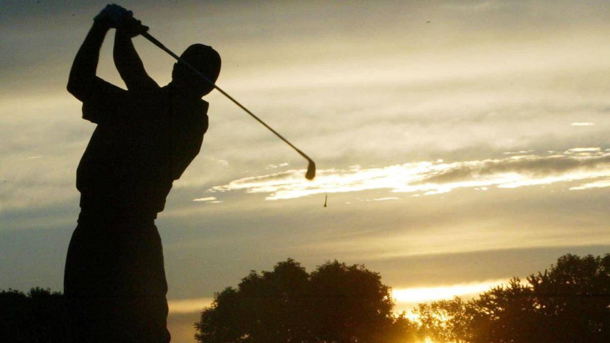 Silhouette of golfer teeing off in the morning sun