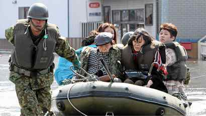 A soldier pulls a rubber boat carrying evacuated people at Ishinomaki city in Miyagi prefecture on March 13, 2011.