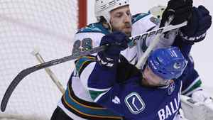 San Jose Sharks' Ryane Clowe, left, battles in front of the net with Vancouver Canucks' Keith Ballard. THE CANADIAN PRESS/Jonathan Hayward