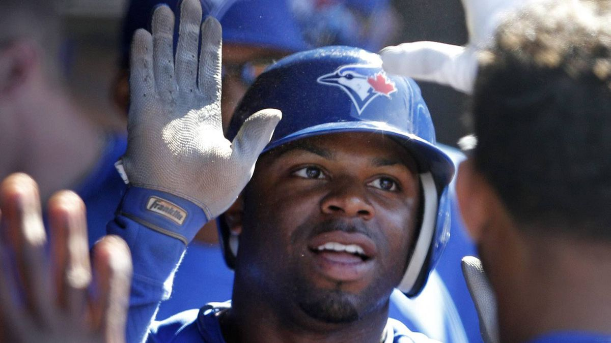 Toronto Blue Jays' Rajai Davis is congratulated in the dugout after scoring on a single by teammate Colby Rasmus in the 12th inning of a baseball game against the Cleveland Indians in Cleveland on Saturday, April 7, 2012. (AP Photo/Amy Sancetta)