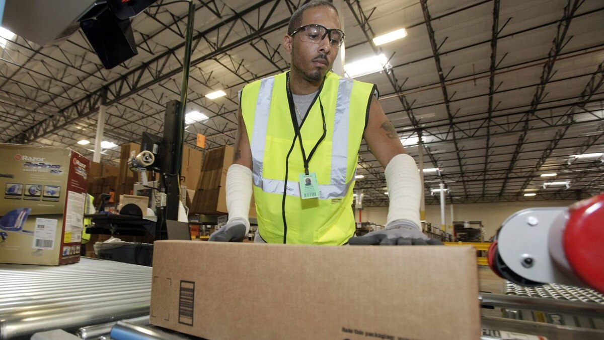 A worker sends a package on its way at Amazon.com's warehouse in Goodyear, Ariz.