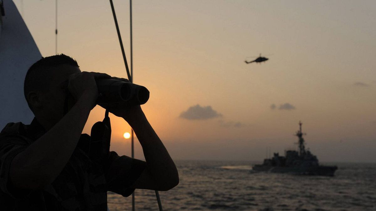 "In this photo released on Monday, Dec. 8, 2008 by the French Defense ministry, a French Navy officer from the EPE, an embedded protection team, is seen aboard the French luxury yacht ""Le Ponant"" checking the horizon using binoculars while a Lynx helicopter is about to land on French anti-submarine frigate ""Jean de Vienne"", as part of the ""Atalante"" protection mission of ships in the gulf of Aden, off Somalia's coasts."