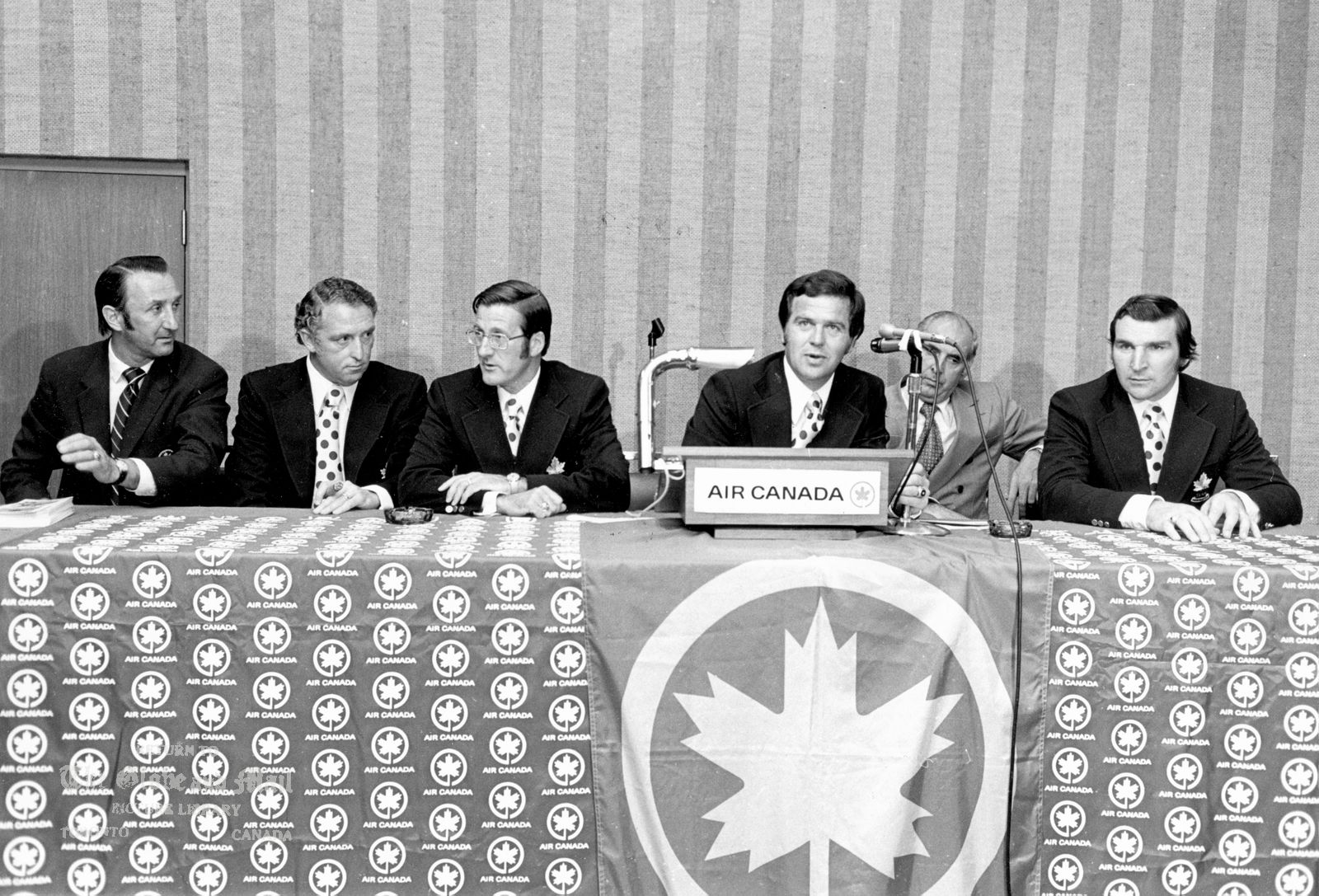 The notes transcribed from the back of this photograph are as follows: JULY 17, 1972 -- TEAM CANADA TV ARRANGEMENTS -- Team Canada officials gather in Toronto on July 17, 1972 to make announcement concerning television arrangements for upcoming Canada-Russia Summit Series. From left, Aggie Kukulowicz, Bob Haggert, Alan Eagleson, head coach Harry Sinden, Arthur Harnett and John Ferguson sit at table sporting Air Canada logos. All but Harnett are due to leave this evening for Russia to complete arrangement for the games at Moscow. The series is set to start in Montreal on Sept. 2, 1972. Photo by Tibor Kolley / The Globe and Mail. Originally published July 18, 1972