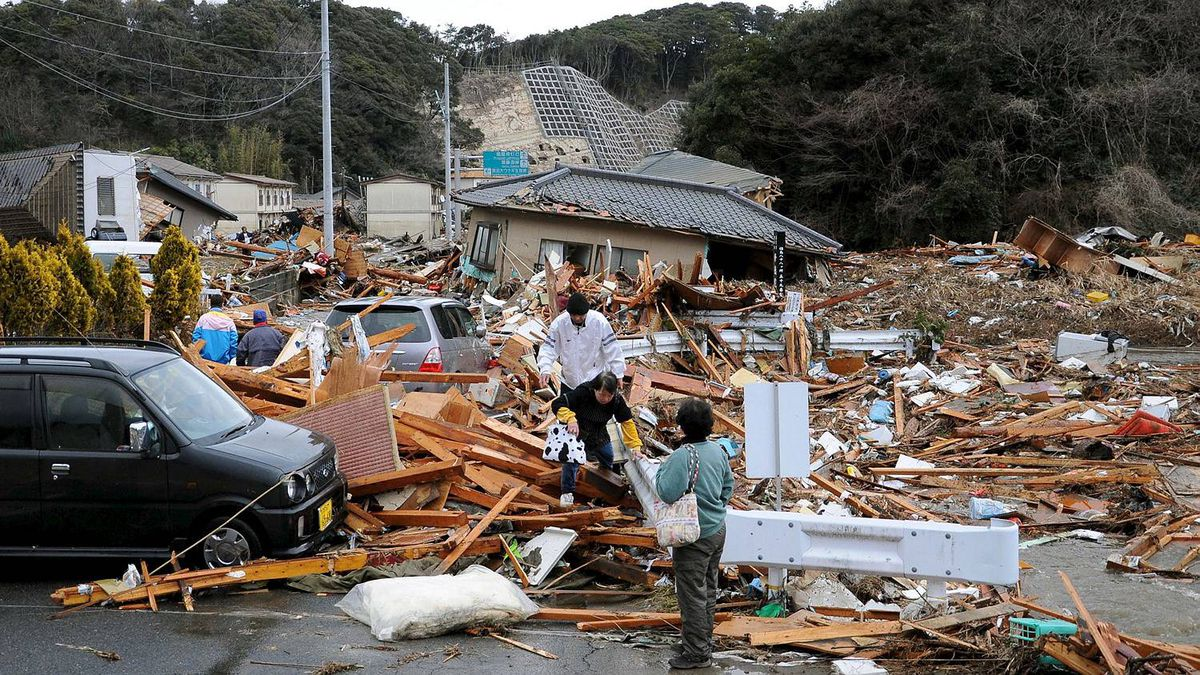Residents walk through buildings collapsed by a powerful earthquake in Iwaki, Fukushima prefecture, Japan, Friday, March 11, 2011.