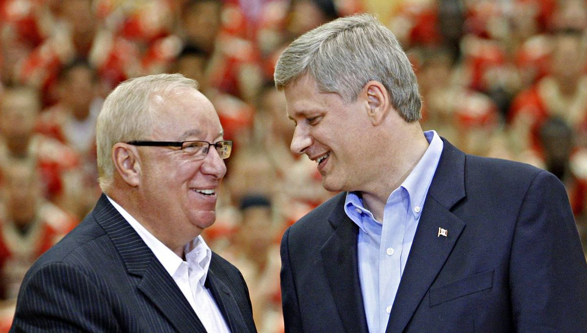 Prime Minister Stephen Harper shakes hands with former Montreal Canadiens coach Jacques Demers at Laval University in Quebec on Aug. 27, 2009.