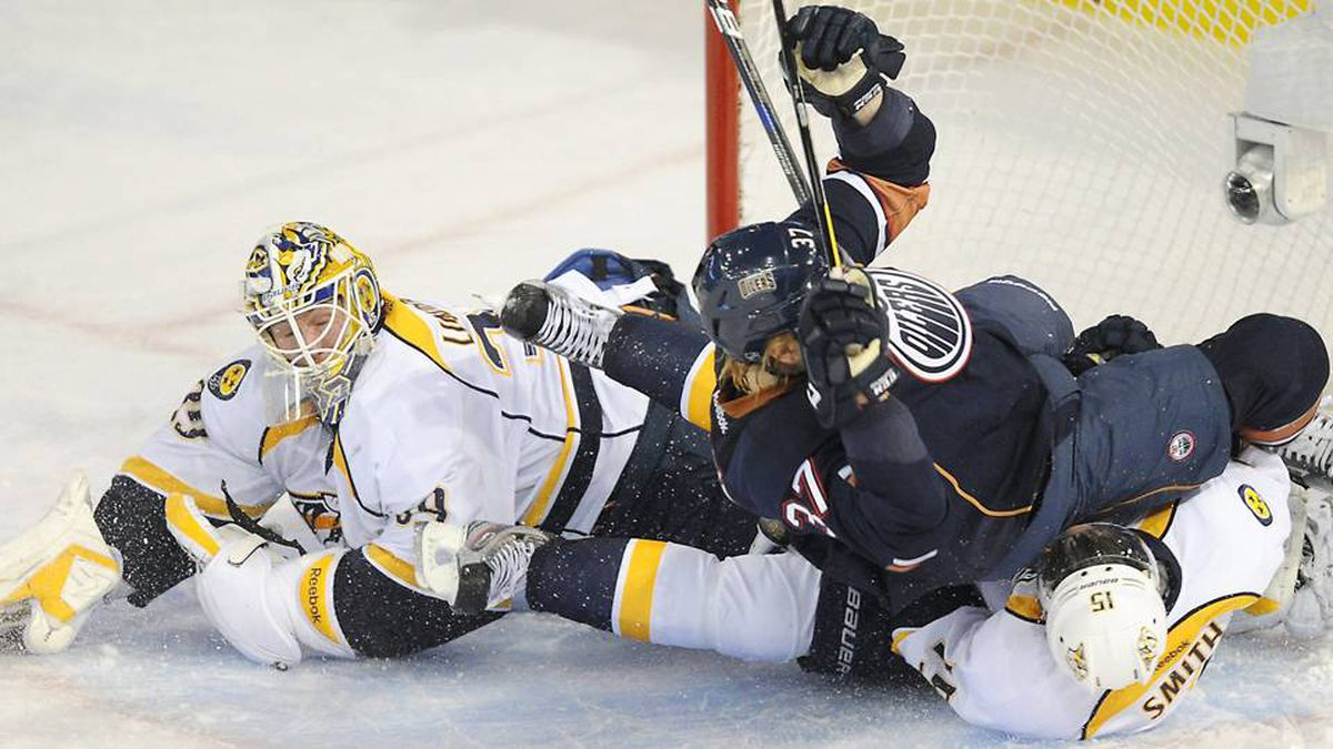 Edmonton Oilers' Lennart Petrell, centre, and Nashville Predators Craig Smith, right, crash the net of goalie Anders Lindback, during second period NHL hockey action in Edmonton, on Monday.