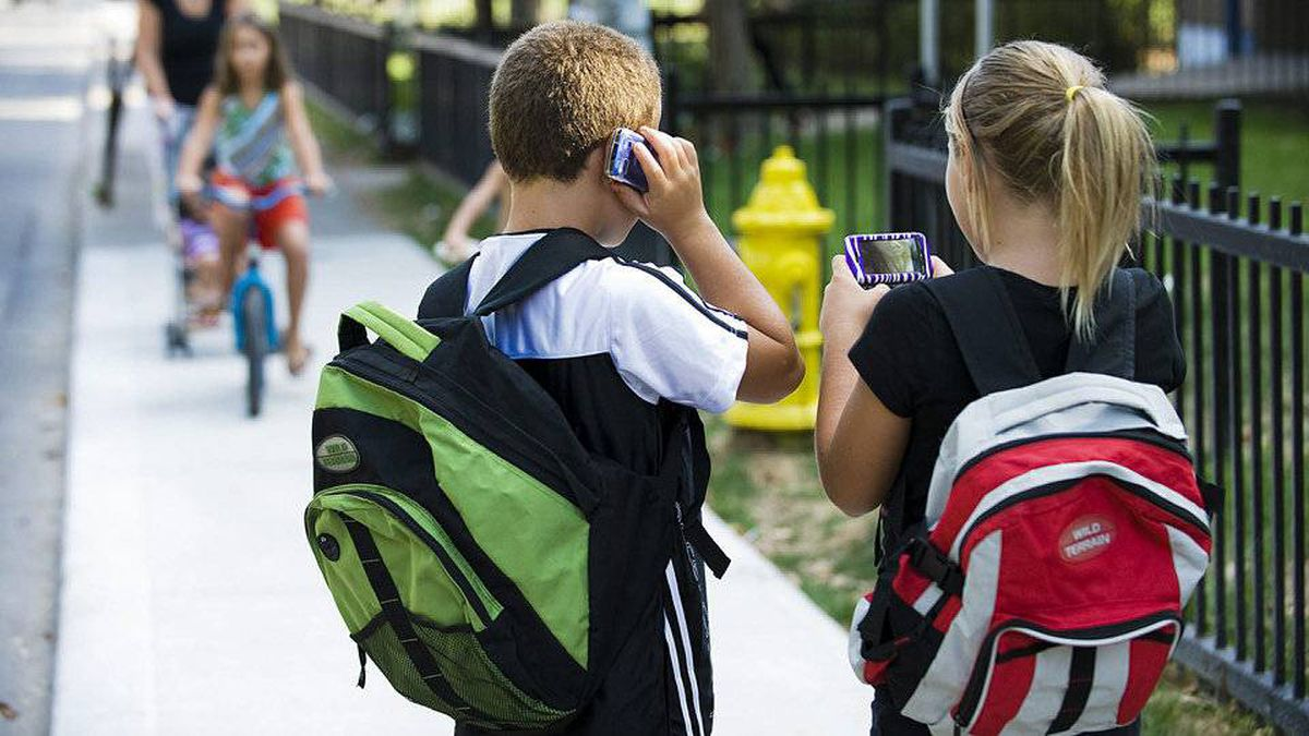 Emily Faria, 11, and her brother Matthew Faria, 8, use their new cellphones in Toronto on Tuesday, August 30, 2011.