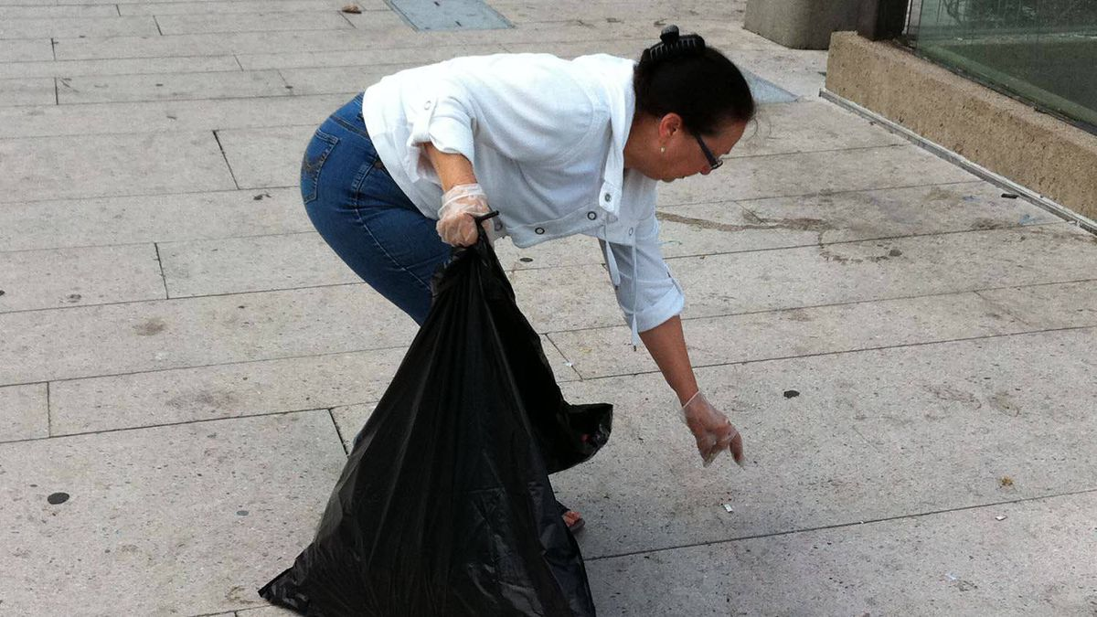 Vancouver resident Edna Bell picks up trash on Robson Street, the morning after a clash between rioters and police, Vancouver, June 16, 2011.