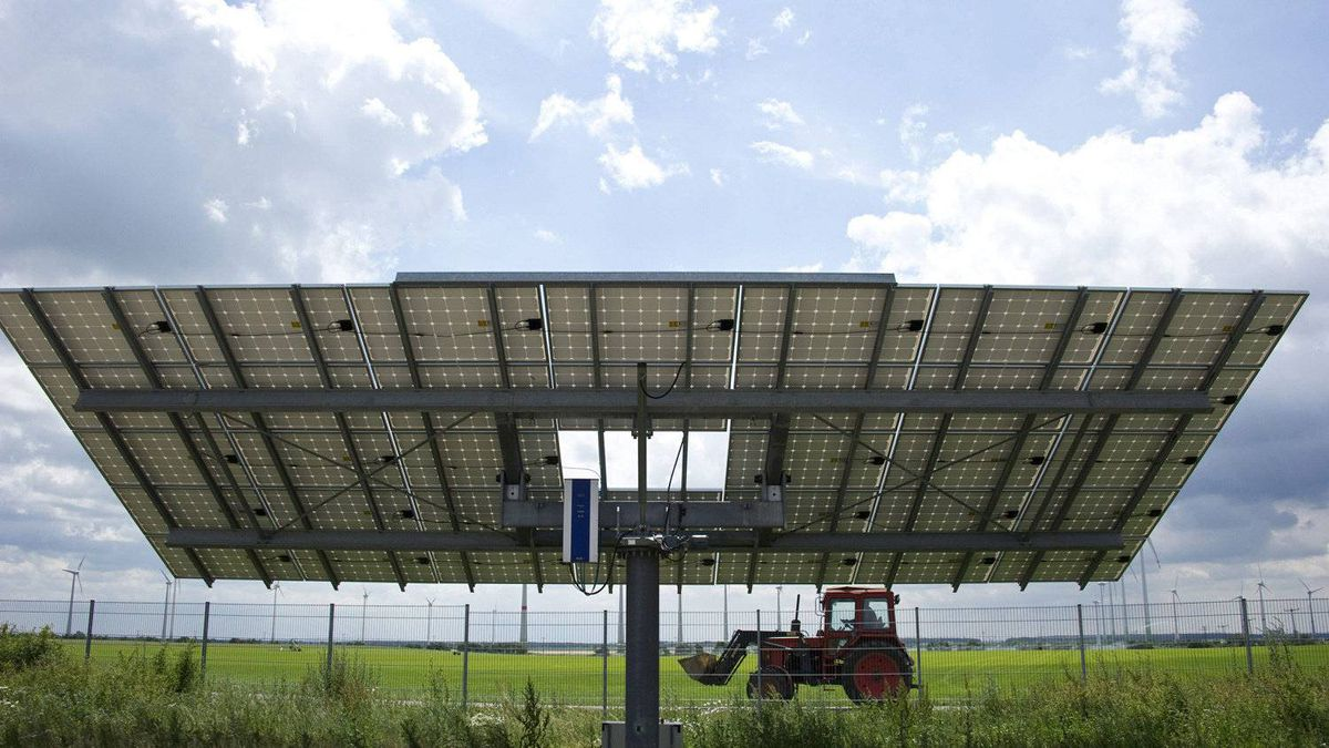 A tractor drives past a solar panel in Germany. JOHN MacDOUGALL/AFP/Getty Images)