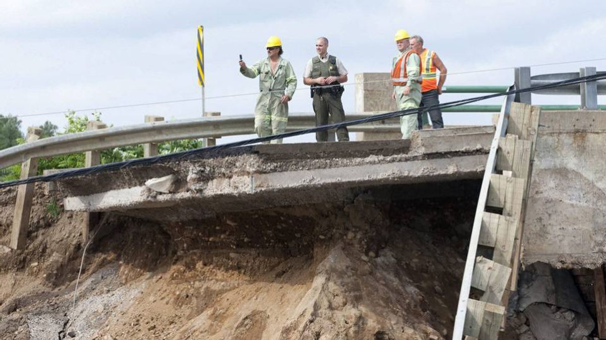 Police and Hydro Quebec workers survey the scene where a section of road on a causeway collapsed following an earthquake in Bowman, Quebec Wednesday June 23, 2010.