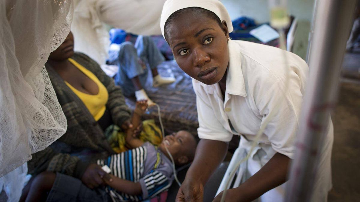 A nurse fixes the IV drip of a young boy suffering from malaria at a hospital in Lubumbashi.