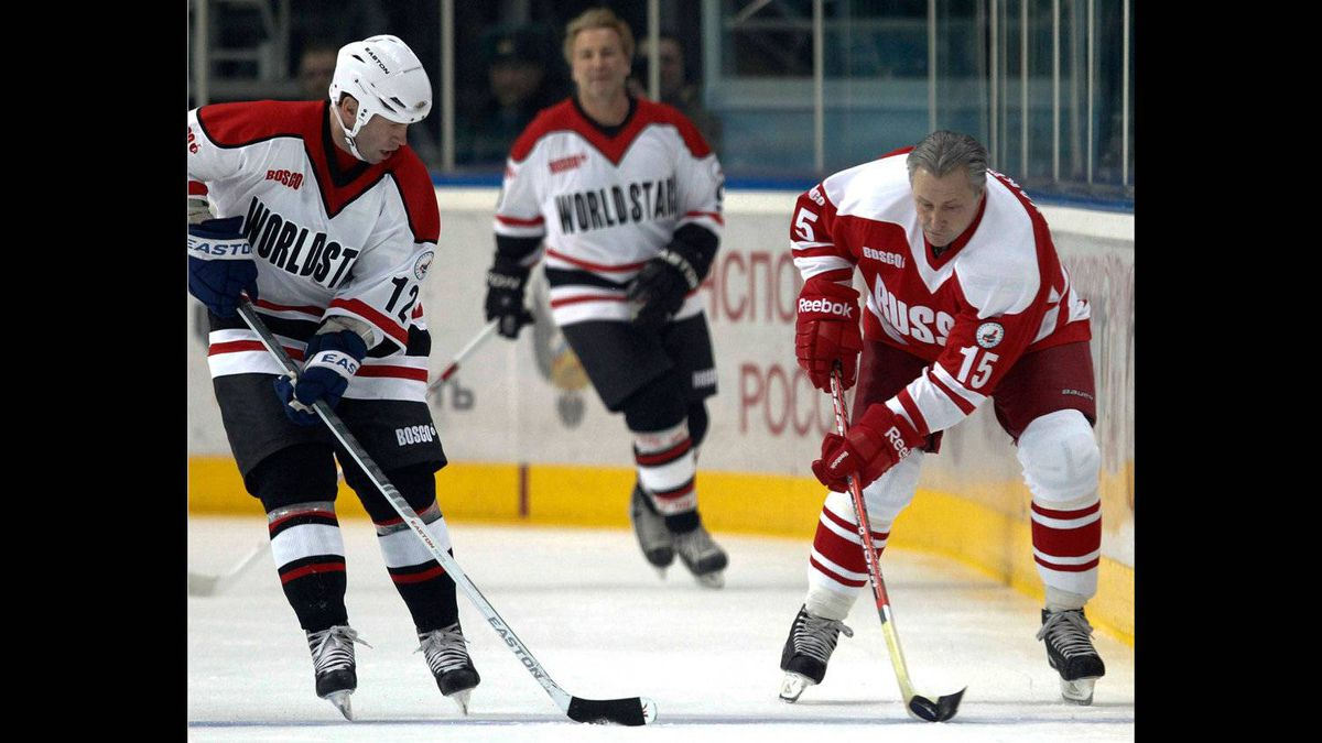 Legendary Russian hockey player Alexander Yakushev, right, fights for the puck with Canadian Dave McLlwain during an exhibition game in Moscow on Feb. 25, 2012 between teams of Russian and world stars to mark the anniversary of U.S.S.R.-Canada 1972 Summit Series.