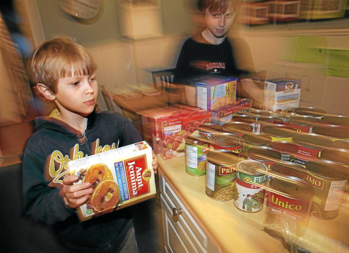 Brothers Adam, 7 (left) and J.J., 10, run food boxes and cans around the kitchen as part of the game Set Up Shop from the book Sneaky Fitness: Fun, Foolproof Ways to Slip Fitness Into Your Child's Everyday Life.
