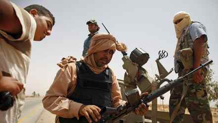 Libyan rebels try to fix a rifle near the front line outside the village of Tiji in western Libya, July 31, 2011.