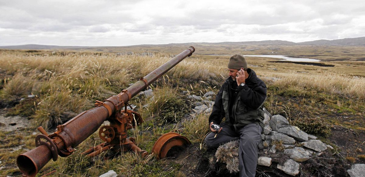 Argentine Falklands War veteran Marcelo Postonia talks on a cellular phone as he sits next to the cannon he used during the conflict near Port Stanley, March 12, 2012. )