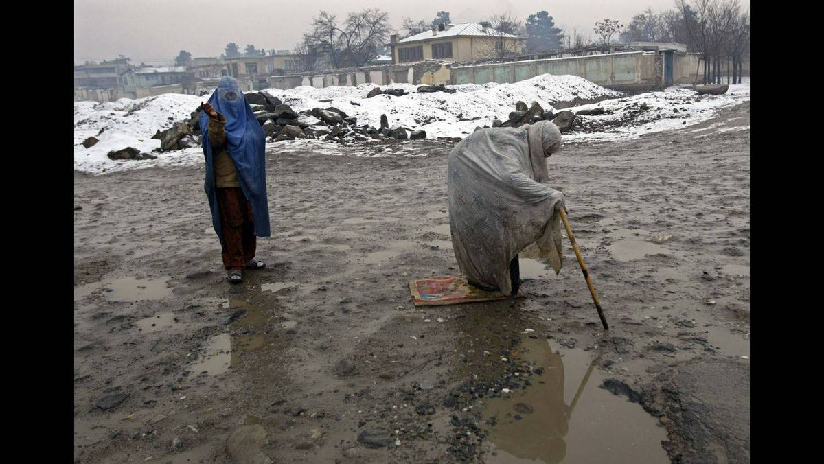 Women beg on a road as snow falls in Kabul, January 13, 2009.