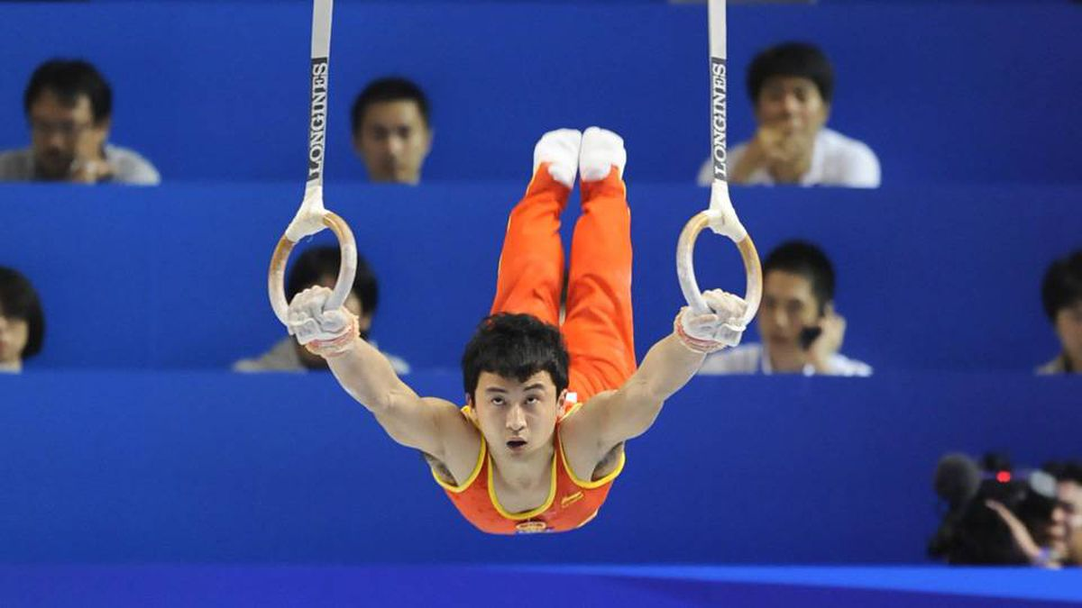 Feng Zhe of China performs on the rings during the men's team event.