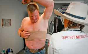 Steer wrestler Lee Graves prepares for competition by having his chest wrapped on day six of the Calgary Stampede Rodeo.