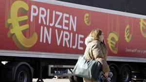 A woman walks in front of a delivery truck with the euro symbol which reads 'Prices in free fall, so much more for your money' in Brussels on Monday, March 12, 2012.