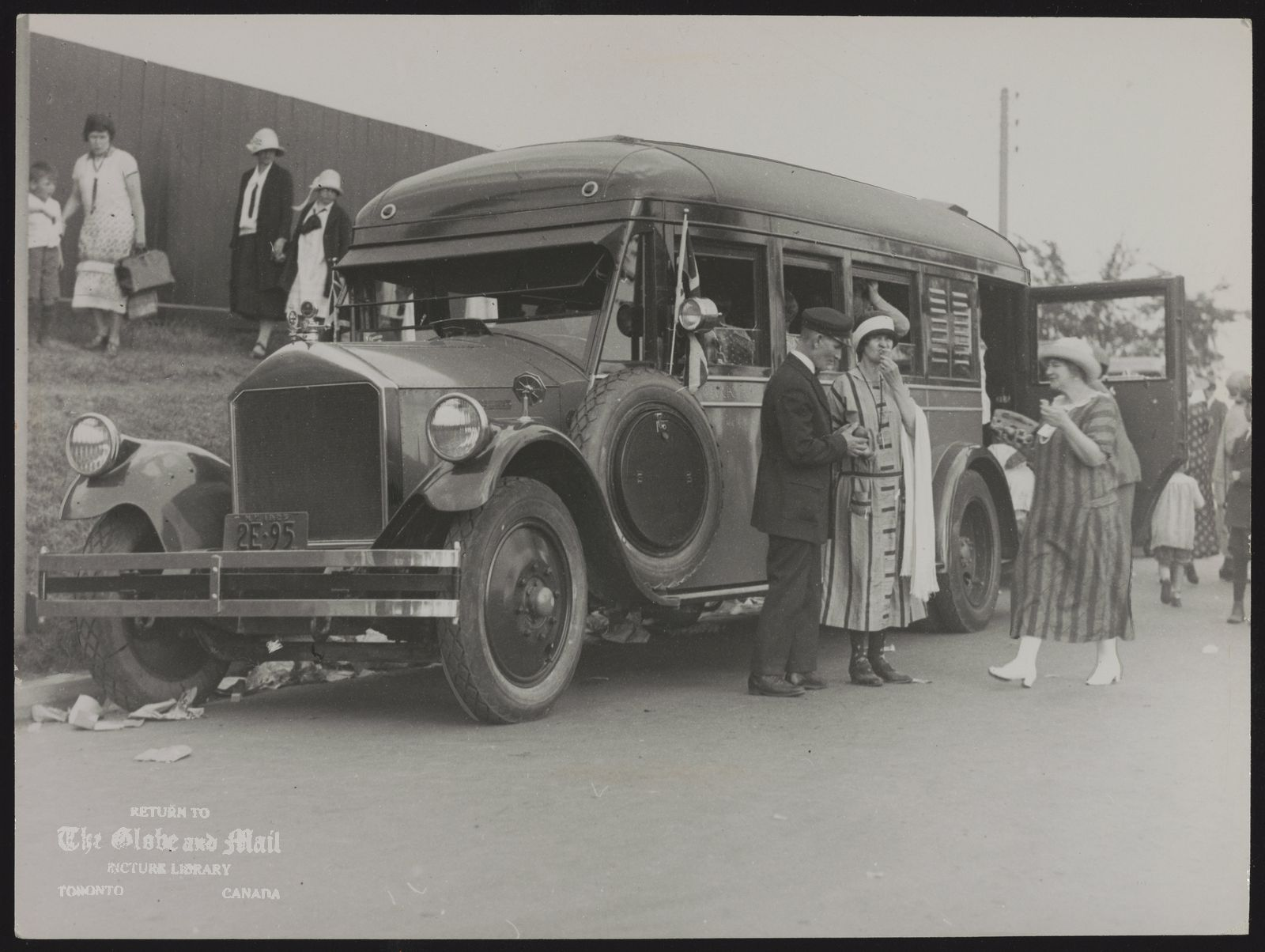 The notes transcribed from the back of this photograph are as follows: Visitors went to the CNE by bus in 1925 just as they do today. [1925 People surround motor coach parked at the Canadian National Exhibition]