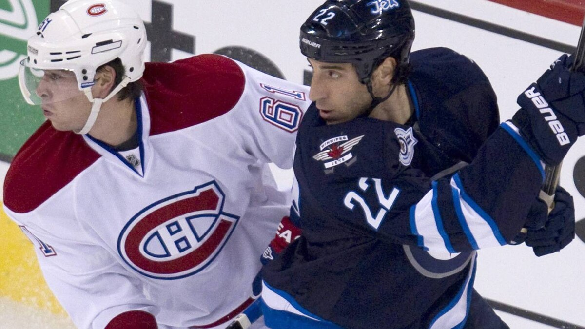 Montreal Canadiens defenseman Raphael Diaz (61) and Winnipeg Jets right wing Chris Thorburn (22) fight for control of the puck during first period NHL hockey action in the Jets inaugural game at the MTS Centre in Winnipeg, Sunday, Oct. 9, 2011. THE CANADIAN PRESS/Jonathan Hayward