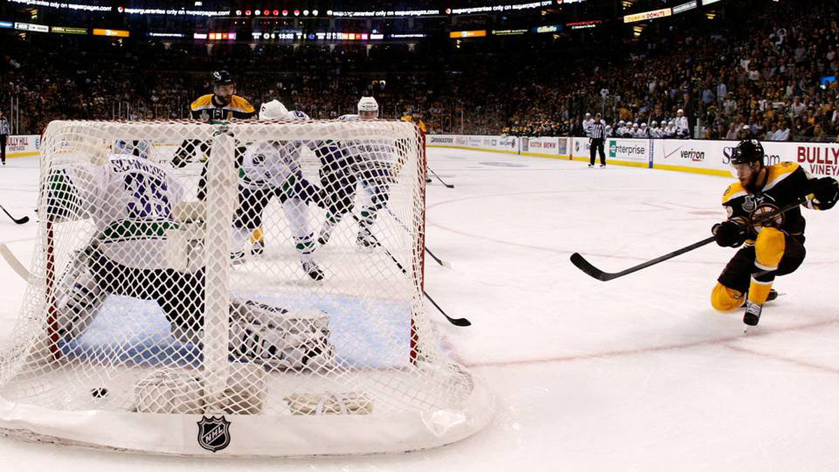 David Krejci of the Boston Bruins scores a goal in the third period against Cory Schneider of the Vancouver Canucks.