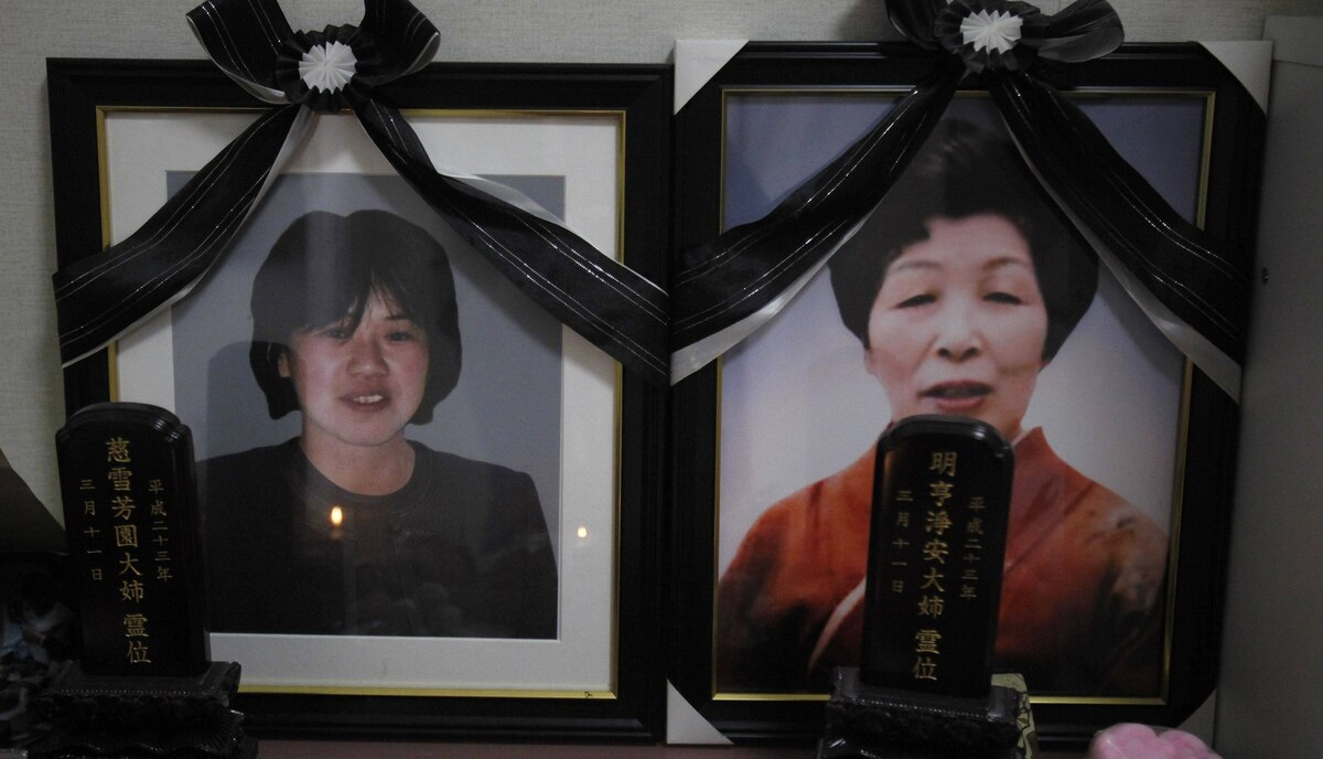 Portrait photos of Yukiko Watanabe, 44, and Kyoko, aged 69, are placed on a table inside Takaaki Watanabe's temporary house. Watanabe, a seaweed farmer, was one of the lucky 5.8 percent from his hometown whose boat survived the March 11, 2011 tsunami, that swept away his wife, mother and his house, that was built on land handed down to him through 13 generations.