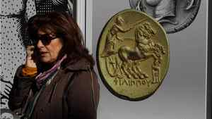 A woman speaks on her phone in front of a Greek bank's adverting banner with ancient coins in Athens, on Friday, Jan. 13, 2012.