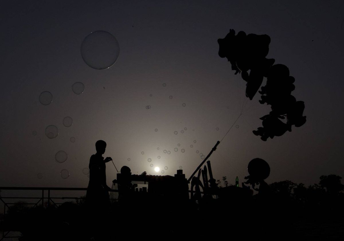 A man is silhouetted against the setting sun while selling balloons and bubbles from a stall at the Rawal Lake Park in Islamabad March 23, 2012.