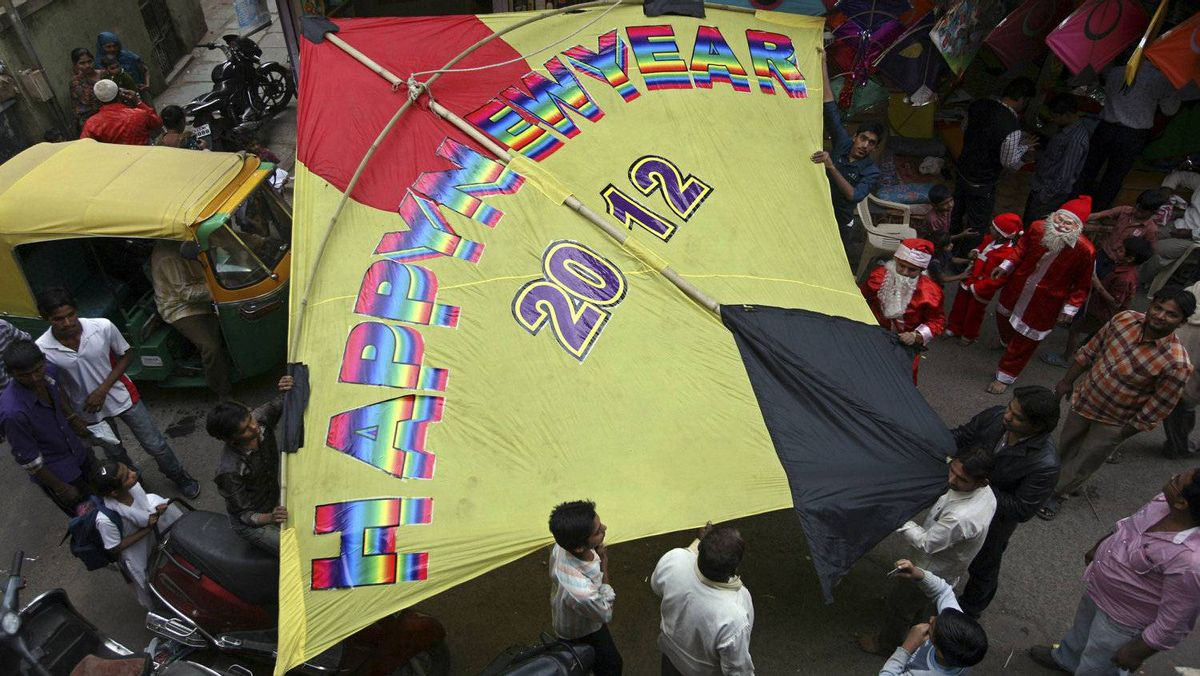 People carry a 30-feet (9.1 m) kite to fly during New Year's Day celebrations in the western Indian city of Ahmedabad December 31, 2011.